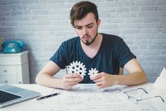 Engineering man working on blueprint for designing mechanical pa. Rts is adjusting a 3D printer`s components in office. Engineering tools and Business concept royalty free stock image