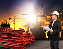 Engineering man working in building construction site and readin. G plan ducument  use for construciton industrial business and land development topic Stock Photo