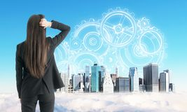 Engineering and mechanism concept. Back view of young businesswoman looking at creative New York city skyline on blue sky background with drawn cogwheels royalty free stock photo