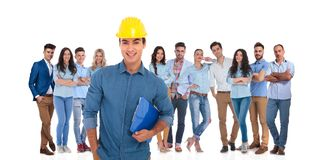 Engineering student leader holding notepad with his team behind. Smiling engineering student leader holding notepad while his casual team is standing behind him royalty free stock image