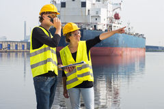 Engineering students. Two technology students discussing an assignment during an internship on site at an industrial harbor Stock Photography