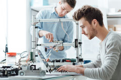 Engineering students working in the lab. A student is adjusting a 3D printer's components, the other one on foreground is using a laptop Royalty Free Stock Photos