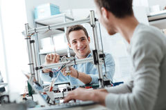 Engineering students working in the lab. A student is adjusting a 3D printer's components, the other one on foreground is using a laptop Royalty Free Stock Images