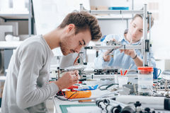 Engineering students working in the lab. A student is using a voltage and current tester, another student in the background is using a 3D printer Royalty Free Stock Photo