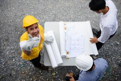 Engineering team look paper plans by top view. Engineering team looking paper plans outdoor at construction site, Engineer team with Asian worker men thumb up Royalty Free Stock Images