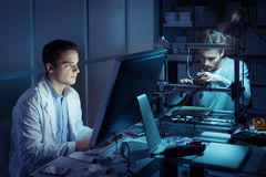 Engineering team working in the lab. At night, a student is working with a computer and the other one is adjusting a 3D printer`s components Stock Image