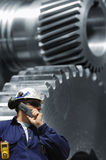 Engineering and timing machine. Engineer in hard-hat inspecting giant timing gears, machinery, conceptual industry. background slightly blurred royalty free stock photos