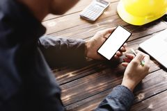 Engineering using phone on desk Royalty Free Stock Images
