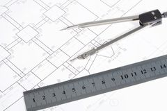 Engineering work. Close-up of blueprints with sketches of projects on workplace and some mechanical tools Royalty Free Stock Images