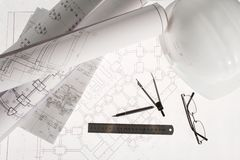 Engineering work. Close-up of blueprints with sketches of projects, eyeglasses, helmet and some mechanical tools Royalty Free Stock Photography