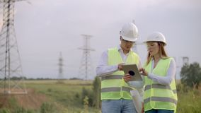 Engineering working on High-voltage tower, Check the information on the tablet computer two employees man and woman. Engineering working on High-voltage tower stock video footage