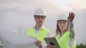 Engineering working on high-voltage tower, check the information on the tablet computer two employees man and woman. Engineering working on high-voltage tower stock footage