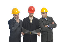 Engineers. Team of engineers looking at a dossier isolated in white Royalty Free Stock Images