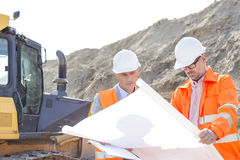 Engineers analyzing blueprint at construction site Stock Images