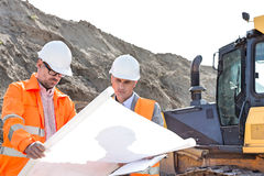 Engineers analyzing blueprint at construction site Stock Photos