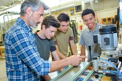 Engineers and apprentices with cnc machine. Apprentices royalty free stock photo