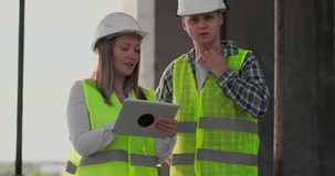 Engineers or architects have a discussion at construction site looking through the plan of construction. contre jour. Engineers or architects have a discussion stock video