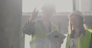 Engineers or architects have a discussion at construction site looking through the plan of construction. contre jour. Engineers or architects have a discussion stock video footage