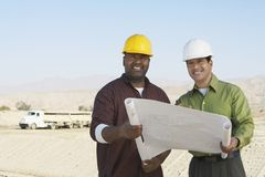 Engineers With Blueprint At Construction Site Royalty Free Stock Images