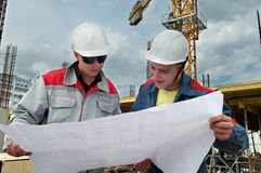 Engineers builders at construction. Two engineer builders examining blueprint at construction site Royalty Free Stock Image