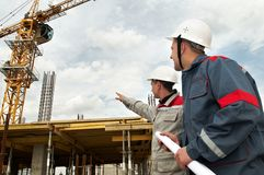 Engineers builders at construction. Two engineer builders with blueprint at construction site Royalty Free Stock Photos