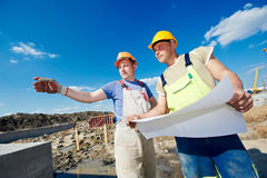Engineers builders at construction site. Two engineer builders with blueprint plan at construction site Stock Photography