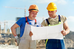 Engineers builders at construction site. Two engineer builders with blueprint plan at construction site Royalty Free Stock Photos