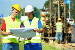 Engineers builders at road works construction site. Two engineer site managers builders with blueprint plan at geology roadwork construction site Royalty Free Stock Photos