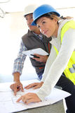 Engineers on building site using tablet. Engineers on building site checking plans Royalty Free Stock Photo