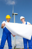 Engineers with construction plan in wind farm Stock Images