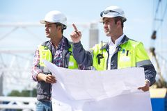 Engineers At Construction Site. Two engineers at construction site are inspecting works according to design drawings Stock Photography