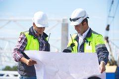 Engineers At Construction Site. Two engineers at construction site are inspecting works according to design drawings Stock Photo
