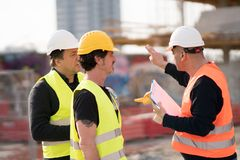 Engineers and construction workers at work. On construction site. Outdoors stock photography