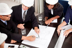 Engineers discussing about a new project. Around a table pointing at a section on the blueprint stock photos