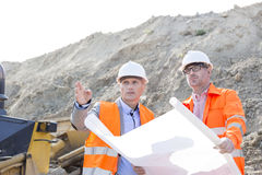 Engineers discussing over blueprint at construction site Royalty Free Stock Image