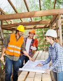 Engineers Discussing Over Blueprint At Site Royalty Free Stock Photography