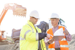 Engineers discussing over documents at construction site Stock Photo