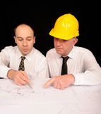 Engineers Discussing Plan. A view of two engineers discussing a construction plan, on a black studio background Royalty Free Stock Photos