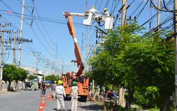 Engineers of electricity in thailand lifts up to fix the electricity stock image