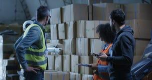 Engineers evaluating a robots work. Medium long shot of engineers evaluating a robots work in a warehouse stock video footage