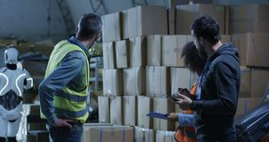 Engineers evaluating a robots work. Medium long shot of engineers evaluating a robots work in a warehouse stock video