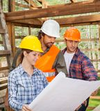 Engineers Examining Blueprint In Wooden Cabin Royalty Free Stock Photos