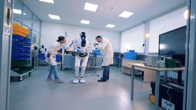 Engineers fixing robot. Robot in scientific lab. Man and woman use tools to fix a white robot stock video footage