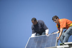 Engineers Fixing Solar Panel Against Blue Sky Stock Photography