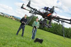 Engineers Flying UAV Helicopter in Park. Happy young male engineers flying UAV helicopter with remote control in park Royalty Free Stock Photo