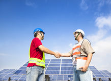 Engineers handshaking before solar power station stock photos