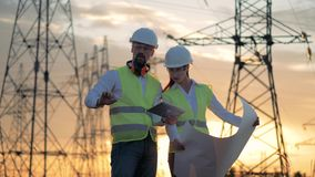 Engineers in hard hat discussing electrical project near power line. 4K stock video footage