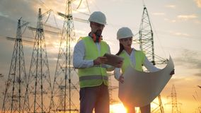 Professional electricians discussing electrical project near power line. Engineers in hard hat discussing electrical project near power line. 4K stock footage