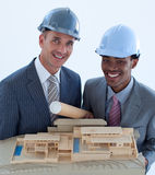 Engineers with hard hats holding a model house Stock Photography