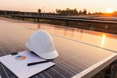 Engineers hat and the graph are placed on the solar panel, alternative electricity source, concept of sustainable resources.  royalty free stock photos
